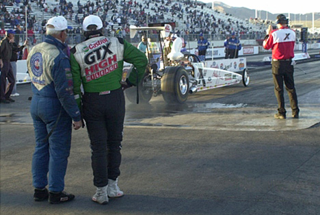 Gary Densham and John Force watch Ashley Force do a burn-out.