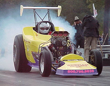 Wild Bill Howry hammers it at Texas Raceway as two Bob and Doug McKenzie look-alikes take cover. Photo by Chris Graves