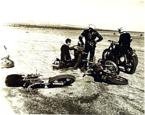 TV Tommy Ivo checks on Kenny Safford as Don Prudhomme and another rider look on after the big desert motorcycle crash. Photographer unknown