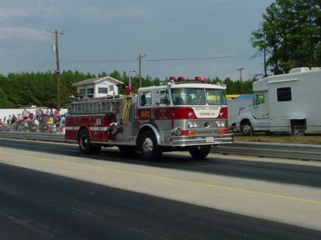 What looks like a parade down the track is actually the local VFD rushing to the seen of a grass fire that ignited when a racer blew a motor and pulled off the return road. Roger Richards photo